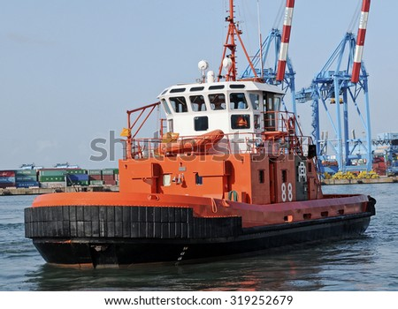 GENOA, ITALY - AUGUST 2, 2011: The Italian port city of Genoa. In the picture a tug with cranes terminal Sech company on the background.