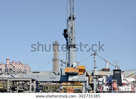 GENOA, ITALY - FEBRUARY 21, 2013: The lighthouse historical symbol of the port city and the coal plant of Enel in front. In the same area with the cranes used to load and unload coal from ships.