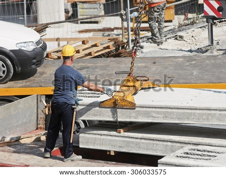 GENOA, ITALY - MARCH 2014: Construction workers to work in a large urban yard. Security and compliance.
