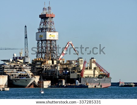 GENOA, ITALY - SEPTEMBER 24, 2015: The Saipem 10000, an oil drilling ship of Saipem, a subsidiary of Eni. Pictured the wreck of Costa Concordia and the platform Saipem.