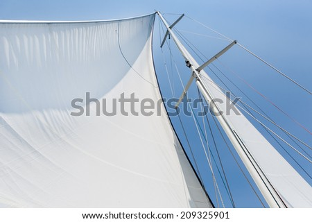 Genoa sail is hoisted on sailing boat mast - stock photo