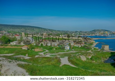 Genoese fortress in Theodosia. Ancient wall and tower, armenian medieval church of the Iberian Icon of the Mother of God, town landscape. Top panoramic view. - stock photo