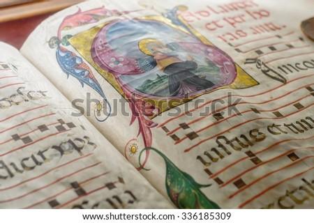 Genova, Italy - July 2015 - Medieval ancient illustrated illuminated monastic manuscript with sheet music Gregorian chant, illustrative editorial, artistic selective focus - stock photo