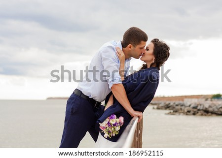 Gentle bride and handsome groom kissing on the pier. Happy newlyweds on the beach. - stock photo