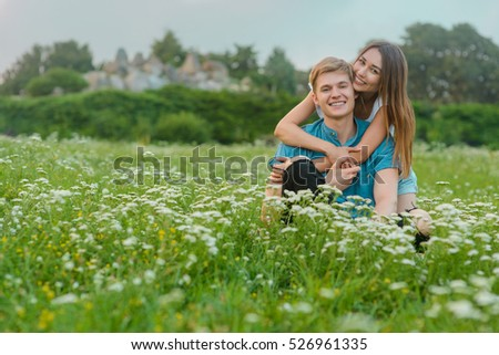 Gentle embracement in nature from two cute beloved ones. Lovely brunette with spread smile embraces her boyfriend from the back.