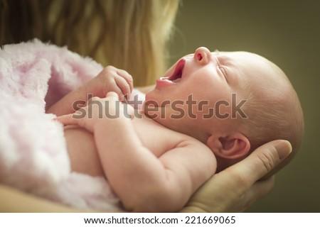 Gentle Hands of Mother Holding Her Precious Newborn Baby Girl. - stock photo