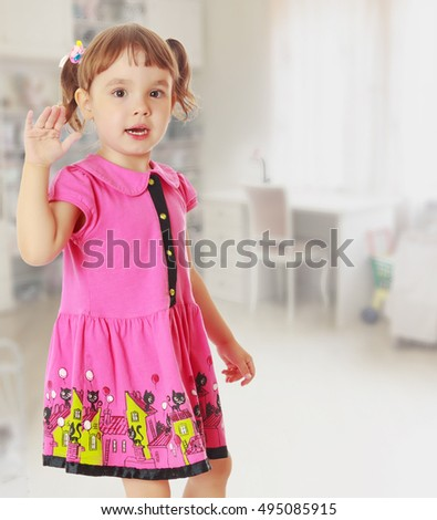 Gentle little girl , pretty in pink , summer dress, waving his hand.In the background children's room, where the shelves are containers with toys, and at the window a large white Desk.