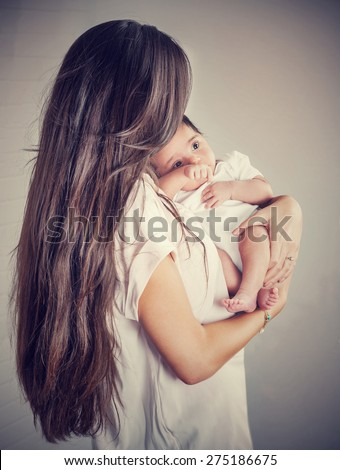 Gentle mother with little baby isolated on gray background, woman with dark long hair holding her precious newborn daughter, love and happy motherhood concept - stock photo