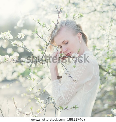 gentle portrait of a beautiful blonde in the spring flowering park - stock photo