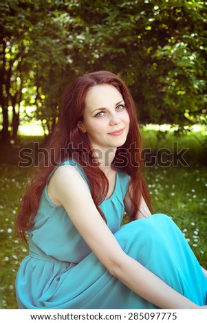Gentle smiling girl. Portrait of a woman. Young woman in nature. Tenderness, romance, kindness. Girl in a romantic gown. A girl with long red hair. Brown hair woman with blue eyes. Girl in dress.  - stock photo