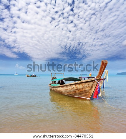 Gentle warm morning on fantastic sea coast. Beautifully decorated native boat Longtail has dropped an anchor in orange beach sand - stock photo
