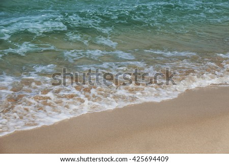 Gentle waves lap onto golden sands. St. Ives, Cornwall, England. - stock photo