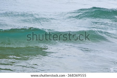 gentle waves splashing on a calm sea on a overcast day - stock photo