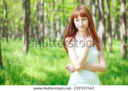 Gentle young woman staying in the forest