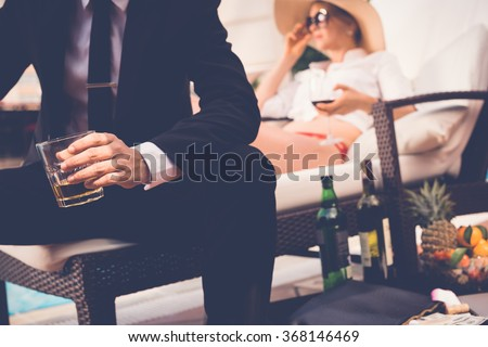 Gentleman drinking whiskey when his wife resting on chaise-longue in the background - stock photo