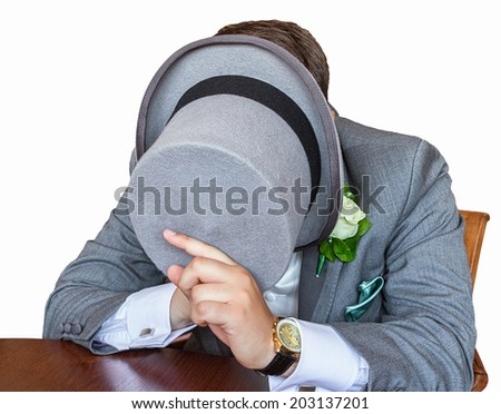 Gentleman hiding his face underneath a top hat - stock photo