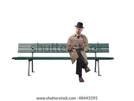 Gentleman reading a newspaper on a park bench - stock photo