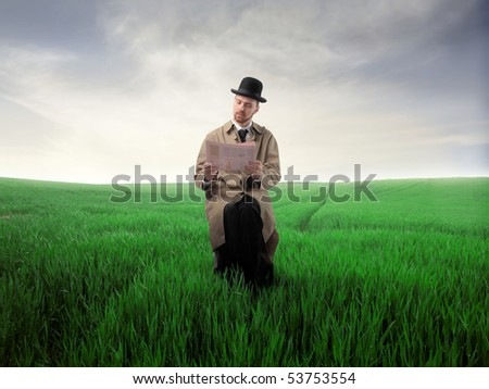 Gentleman sitting on a green meadow and reading a newspaper - stock photo