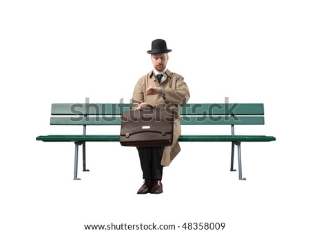 Gentleman sitting on a park bench and looking at his watch - stock photo