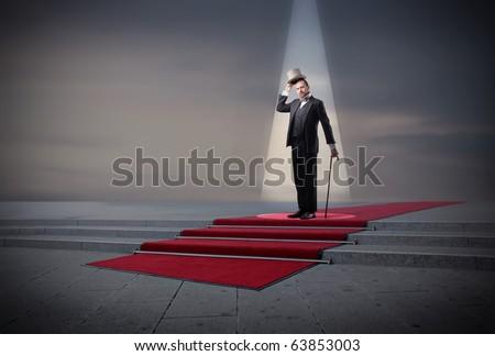 Gentleman standing on a red carpet under a spotlight - stock photo