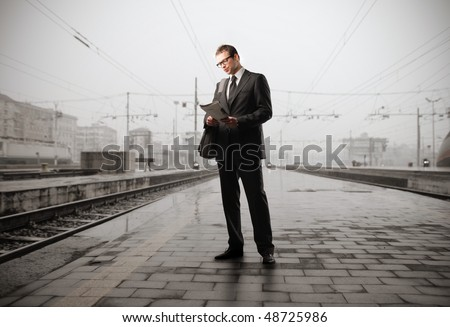 Gentleman standing on the platform of a train station - stock photo
