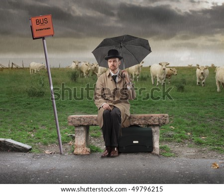 Gentleman with umbrella sitting on a bench and waiting for a bus - stock photo