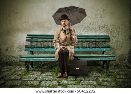 Gentleman with umbrella sitting on a wooden park bench - stock photo