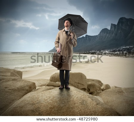 Gentleman with umbrella standing on a rock looking over a seascape - stock photo