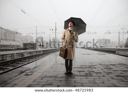 Gentleman with umbrella standing on the platform of a train station - stock photo