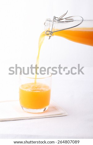 gently pouring orange juice from vintage bottle into a glass - stock photo