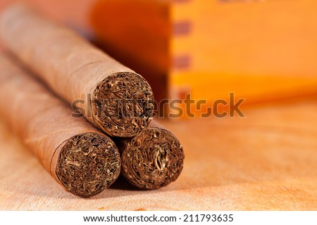Genuine Cuban cigars and wooden varnished cigar box - stock photo