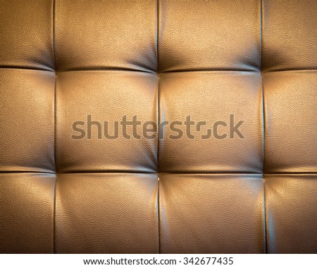 Genuine leather upholstery background for a luxury decoration in golden tone - stock photo