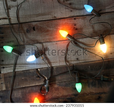 Genuine Vintage 1950s era colored Christmas Lights against Vintage de-nailed rustic and weather beaten old wooden planks for an authentic Vintage Christmas look and feel. Perfect for all your needs - stock photo