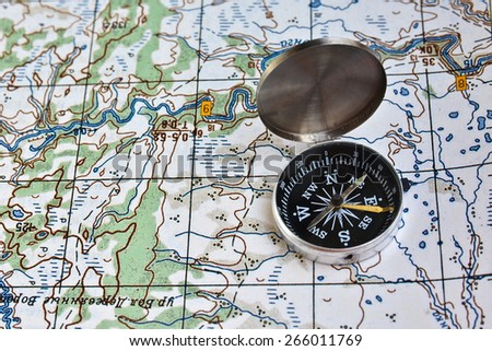 Geographical map and a compass. Photo magnetic compass located on a topographic map. - stock photo