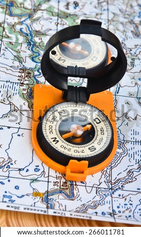 Geographical map and a compass. Photo magnetic compass located on a topographic map.