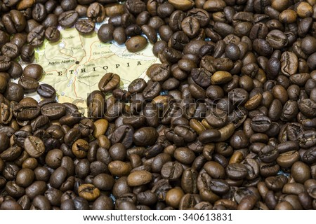 Geographical map of Ethiopia covered by a background of roasted coffee beans. This nation is between the five main producers and exporters of coffee. Horizontal image. - stock photo