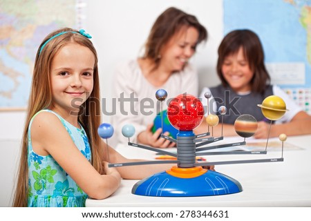 Geography class - little girl learning about the solar system using a scale model - stock photo