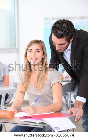 Geography teacher helping pupil - stock photo