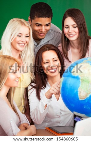 Geography teacher showing something on the globe to her students. - stock photo