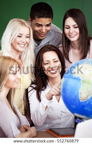 Geography teacher showing something on the globe to her students.