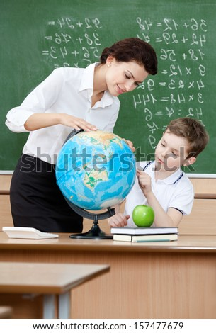 Geography teacher shows something to the pupil at the terrestrial globe - stock photo