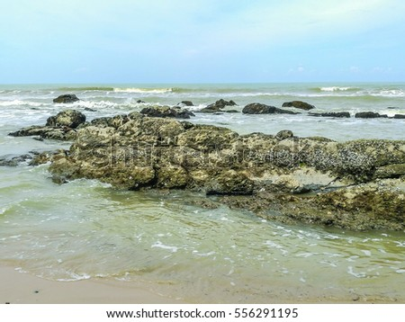 Geologic formation of beach rocks and waves breaking against rocks at Bungai Beach, Miri, Sarawak, East Malaysia. Borneo.
