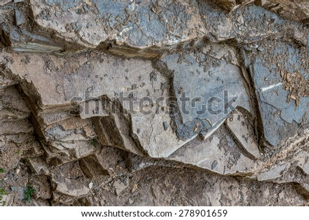 Geology formation of rocks with the soil. Interesting layers of gray stones and dirt shaped like teeth. - stock photo