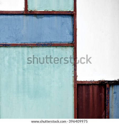 Geometric iron texture steel door background. Green, blue and red metal sheet gate. Composition and elements of visual design. Vintage and hipster. De stijl. Close up.