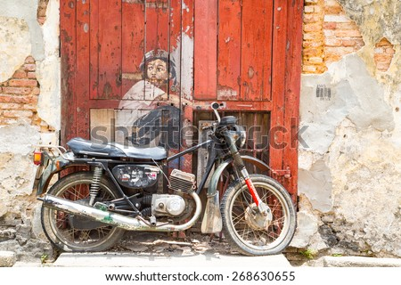GEORGE TOWN,PENANG ,MALAYSIA- March 26, 2015: Public street art Boy on a Bike  on the wall by Lithuanian artist Ernest Zacharevic in Georgetown, Penang, Malaysia. - stock photo