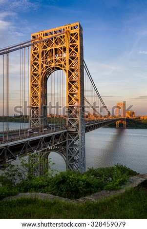 George Washington Bridge crossing the Hudson River connecting Fort Lee, New Jersey and Upper Manhattan, New York City. The towers of the suspension bridge are lit by the sunset light. - stock photo