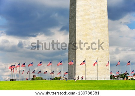 George Washington Monument. People and flag poles, by comparison, give a good idea of the massive size of the obelisk. The world's tallest stone structure and the highest structure in Washington D.C. - stock photo