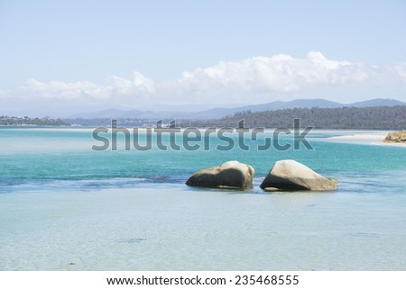 Georges Bay at St Helens, Bay of Fire at east coast of Tasmania, Australia, beautiful scenery with rocks at beach, turquoise ocean water and mountains in blurred background wilderness, copy space. - stock photo