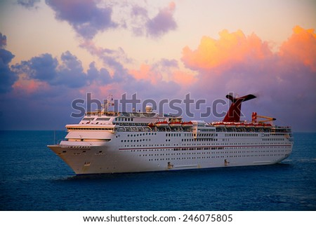 GEORGETOWN, GRAND CAYMAN - MARCH 25, 2009:  Georgetown is a popular for cruise lines in the Caribbean.  This ship is anchored off shore at sunset. - stock photo