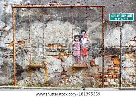"GEORGETOWN, MALAYSIA - JANUARY 19, 2014: Street Art by Louis Gan ""Brother and sister on a swing"". It graces the wall of the Printing Warehouse in an alleyway Chulia Street Ghaut, Step By Step Lane.  - stock photo"